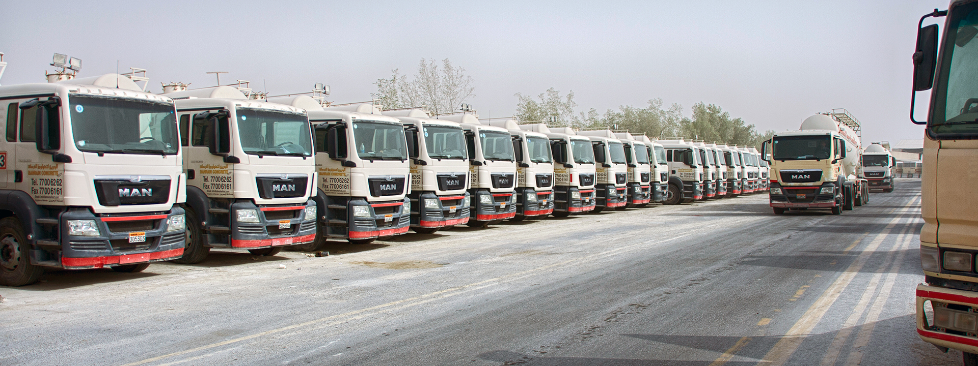 Many large trucks, parked in an organised fashion.