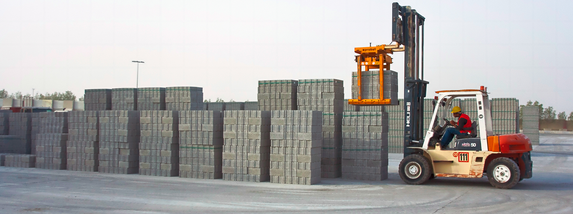 A forklift loading concrete breeze blocks.